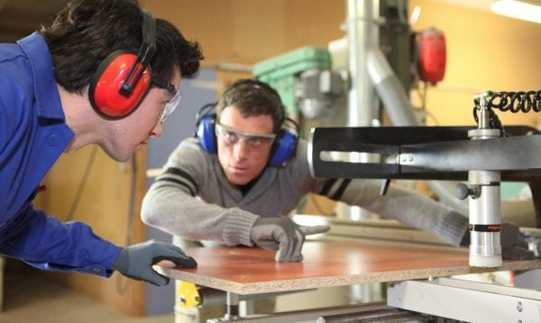 An Experienced Worker Showing An Apprentice How To Cut A Piece Of Wood Using A Machine