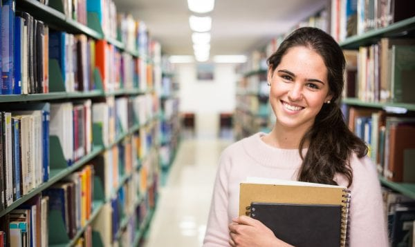 In The Library Pretty Female Student With Books Working In A H