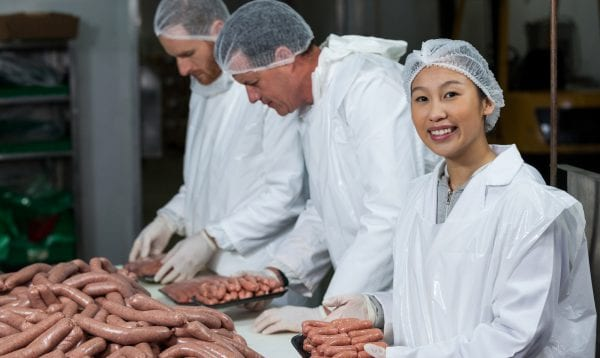 Butchers Packing Raw Sausages