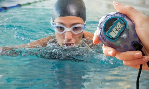 Composite Image Of A Hand Holding A Timer Against Fit Swimmer Coming Up For Air In The Swimming Pool